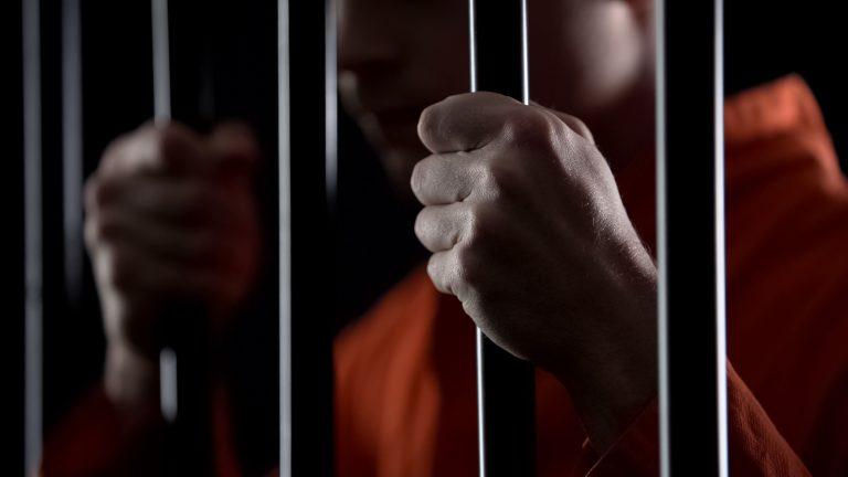 presidiário_segurando_grades_da_prisão